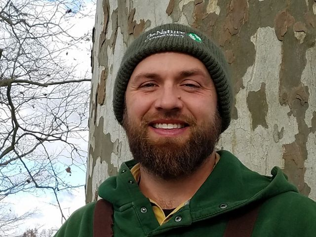 A smiling man with a beard wears a green sweatshirt and green hat standing in front of a tree.