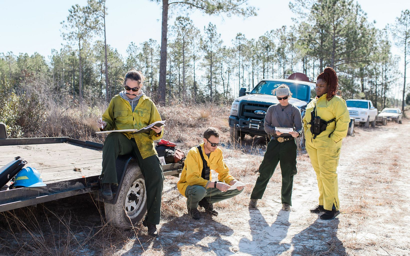 Four people in field gear next to a line of trucks on the edge of a forest.