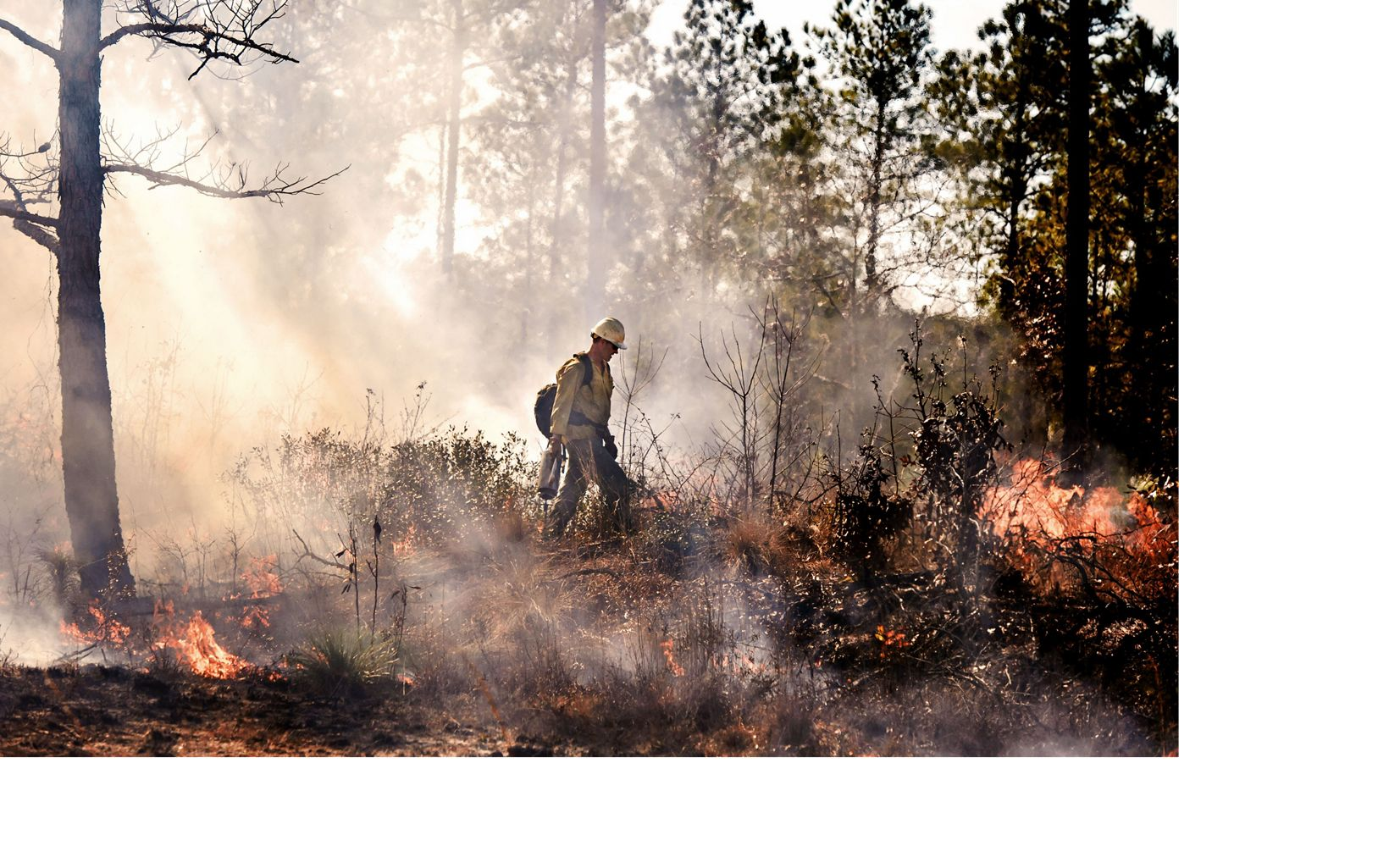 A crew member guiding the burn unit's interior flames by drip torch.