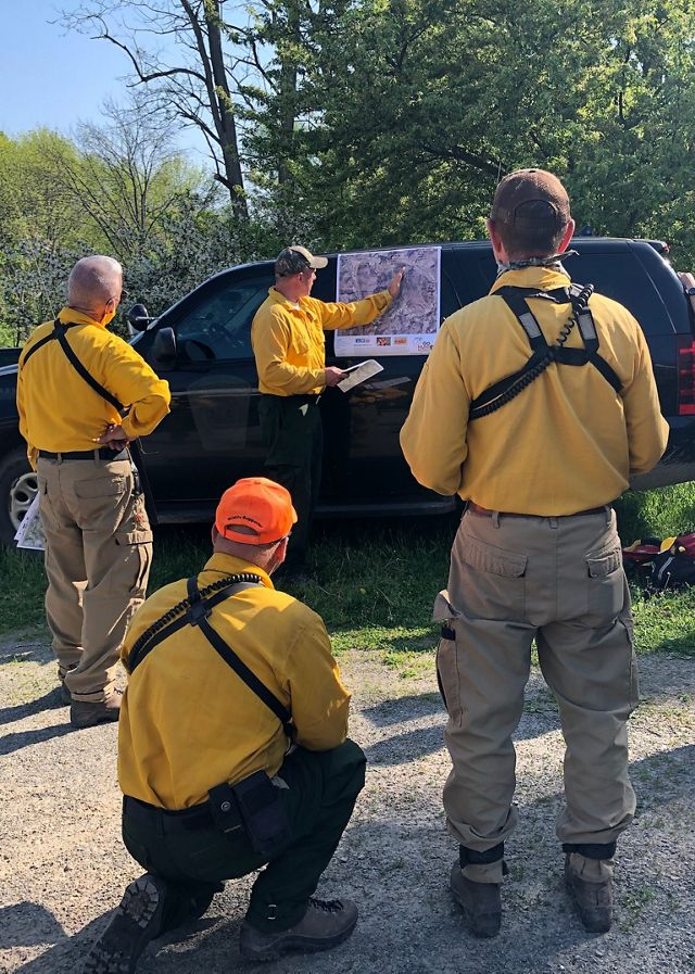 A group of four men wearing yellow fire retardant shirts. Three men are shown from the back gathered around the fourth who is turned, pointing to a large map taped to the side of a black SUV.