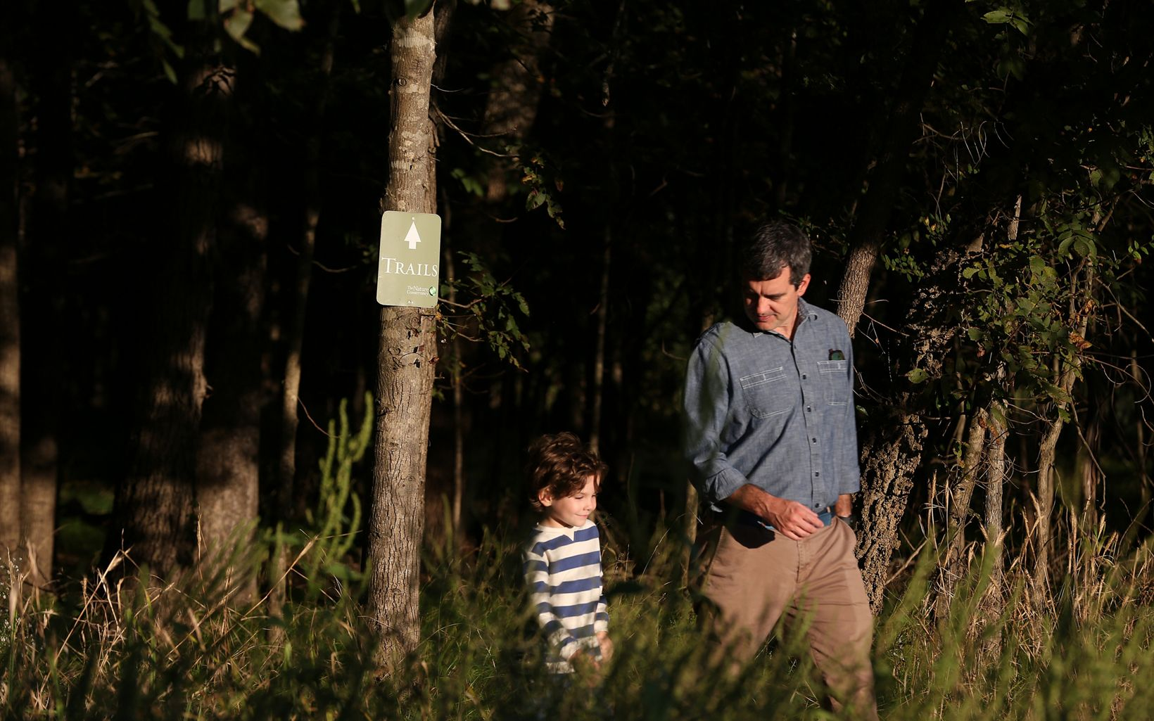 A man and a little boy walking on a trail.