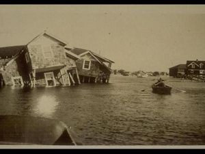 Vintage sepia toned photo showing severe flooding after a storm. A person rows a boat between houses that have been knocked off their foundations and are laying tipped into the deep water.