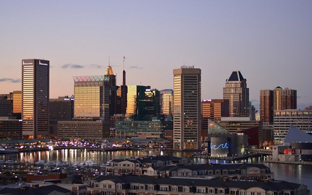 The sun sets over the Baltimore skyline. Tall building dominate the background with low rowhouses lining the foreground.