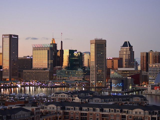 View of the Baltimore city skyline. Tall buildings dominate the background along the harbor. A neighborhood of rowhouses is in the foreground.