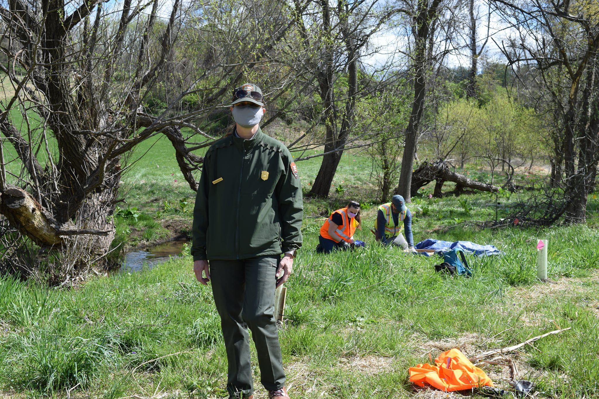 A man wearing a green park rangers uniform poses during a workday at a state park. In the background, two people kneel on the ground planting native plants along an urban stream.