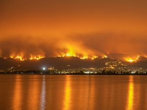 Bright orange flames cover a hillside viewed from the dark orange water.