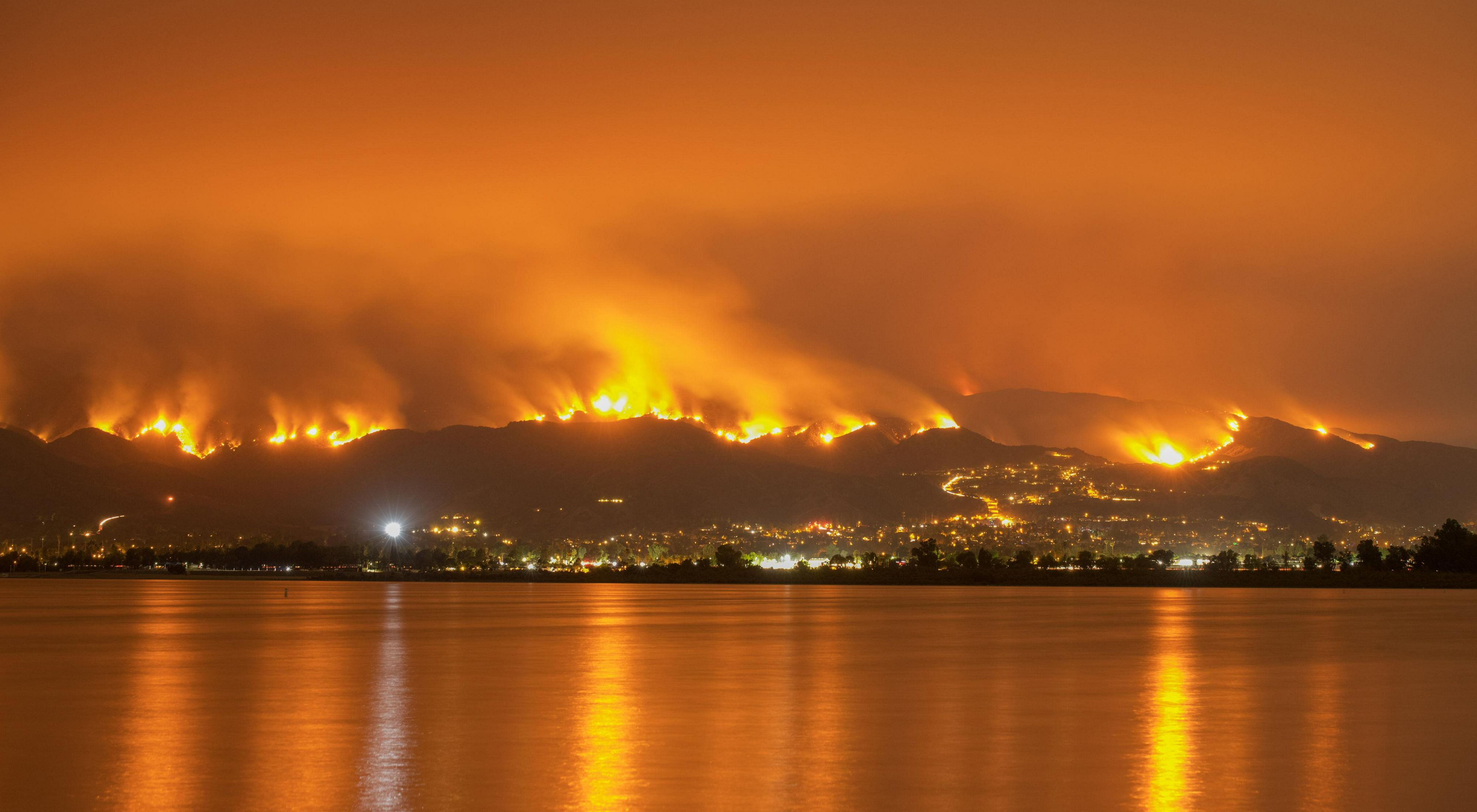 One of the 2018 California wildfires. A glowing orange sky with water in the foreground and flames rising over hills in the background.
