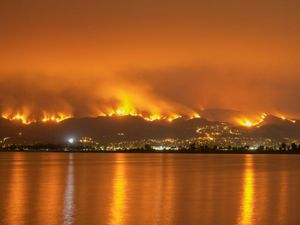 A view across water at hillsides burning with orange flames at night.