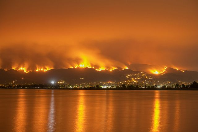 Photo of a wildfire in California, with orange flames reflecting off of the water.