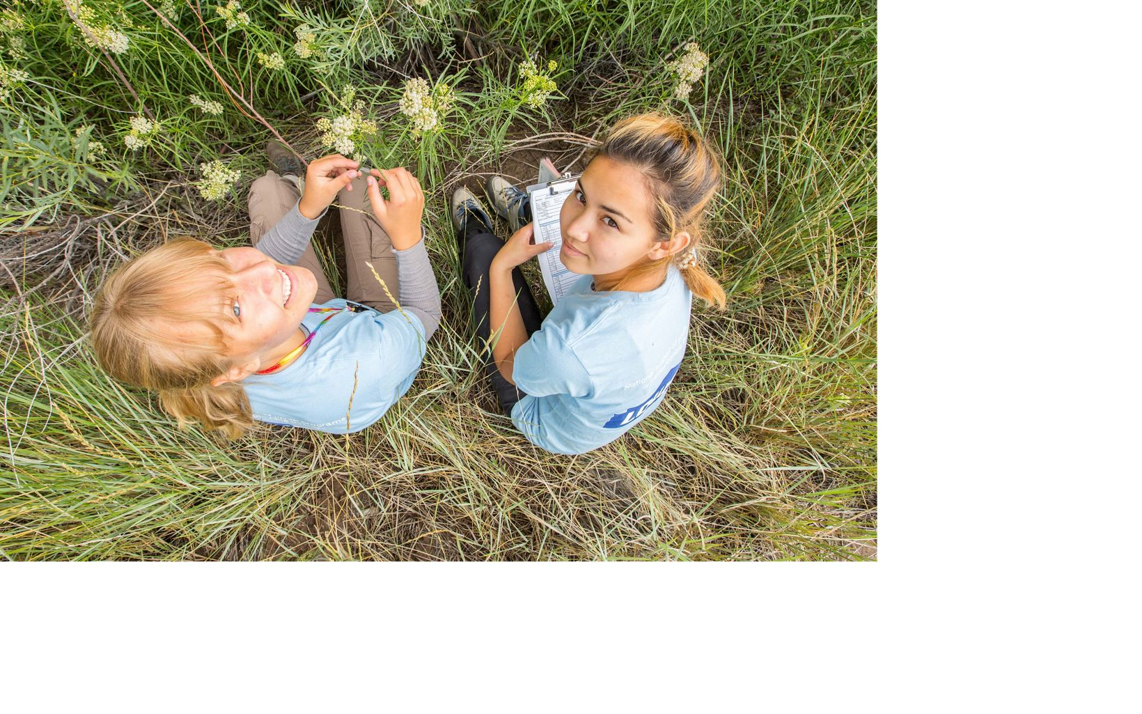 two young girls in a field looking up