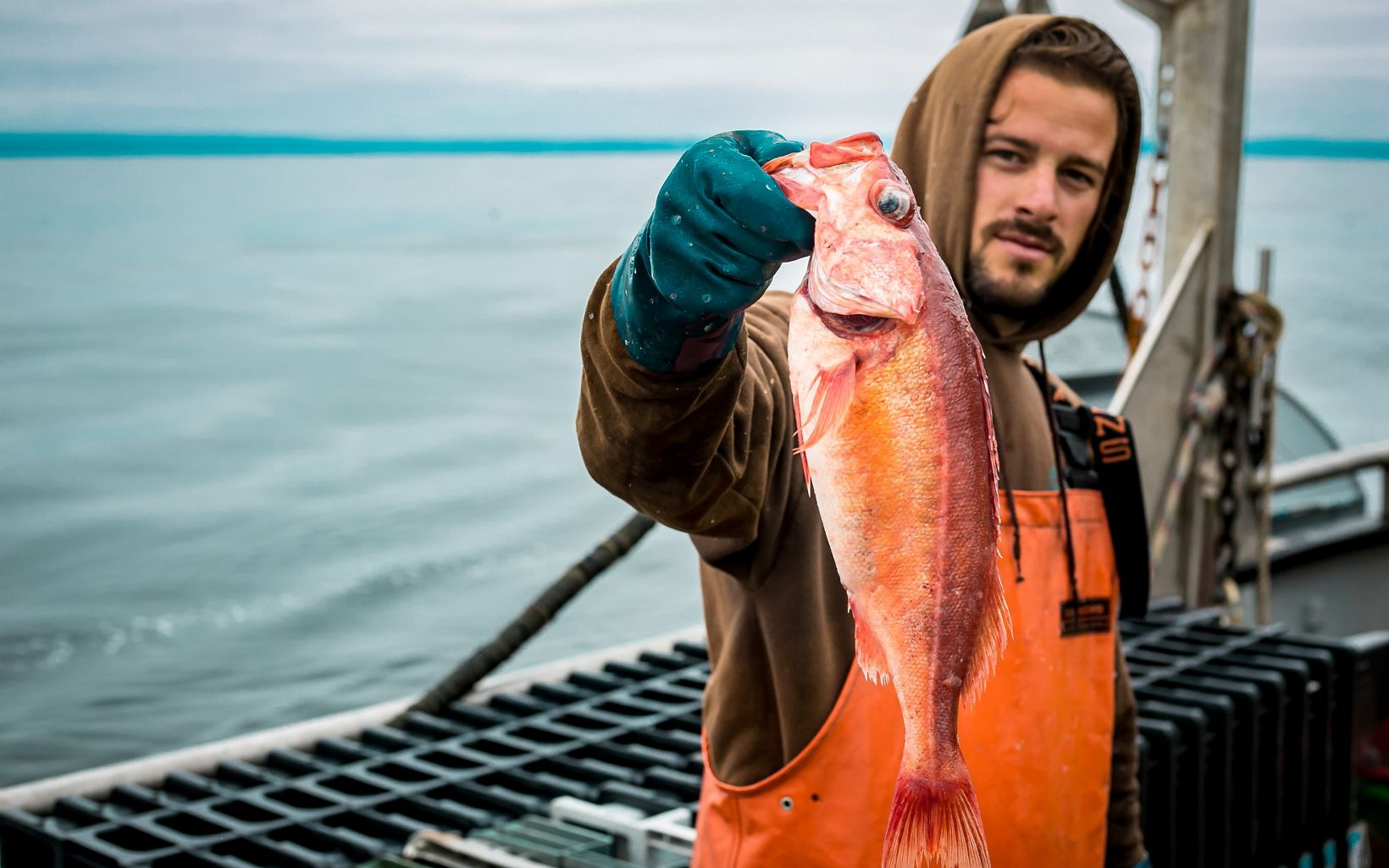 Fisherman in orange waders holding up an orange and red fish by its mouth.