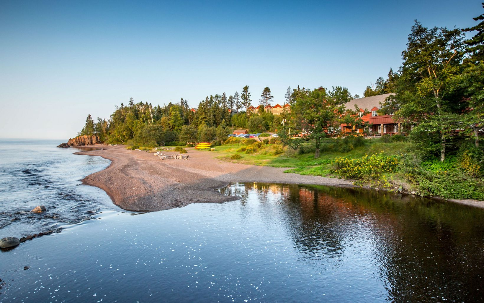 A lodge building is nestled amongst the green conifers along the shores of Lake Superior.
