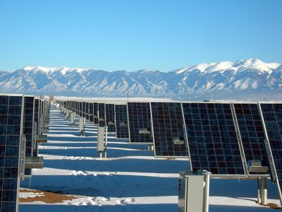 A field of solar panels sits at the base of a mountain range.