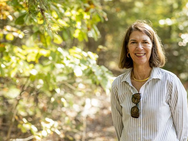 Candid headshot of VA State Director Locke Ogens. A smiling woman poses in nature. Sunlight dapples the trees behind her.