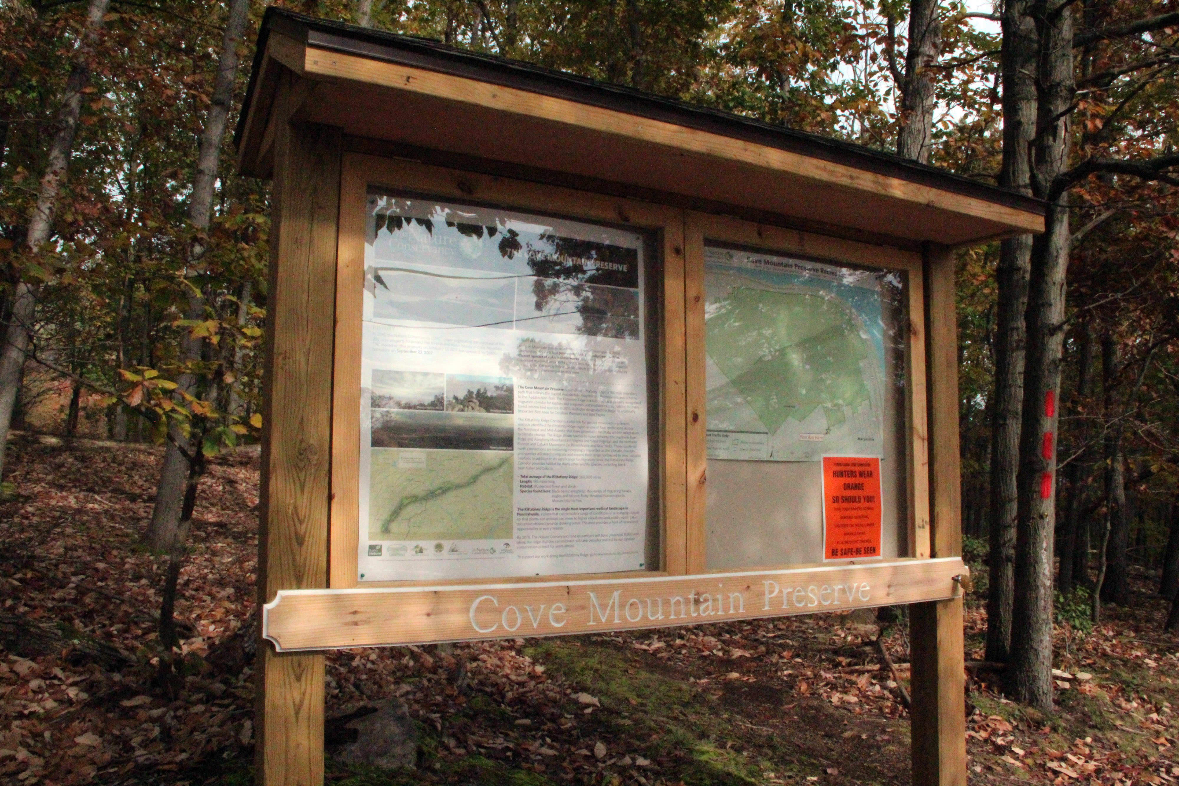 A wooden trail kiosk with a narrow overhangs shades two large information areas showing trial maps and information about the preserve.