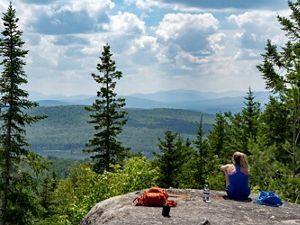 A hiker enjoys a panoramic view from a rocky overlook in Debsconeag Lakes Wilderness Area.