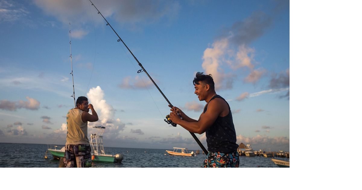 Two men are laughing as they fish with fishing poles from a pier.