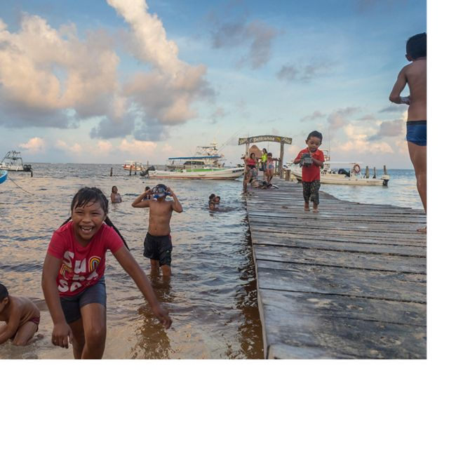 Local children play at the beach and pier in Puerto Morelos, Mexico. Puerto Morelos is a coastal community that benefits from the health of the Mesoamerican Reef off its shores. August 2018.