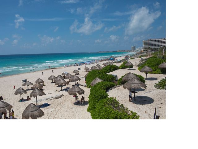 Cancun's famous turquoise blue water and white sand beach, with hotels in the distance.