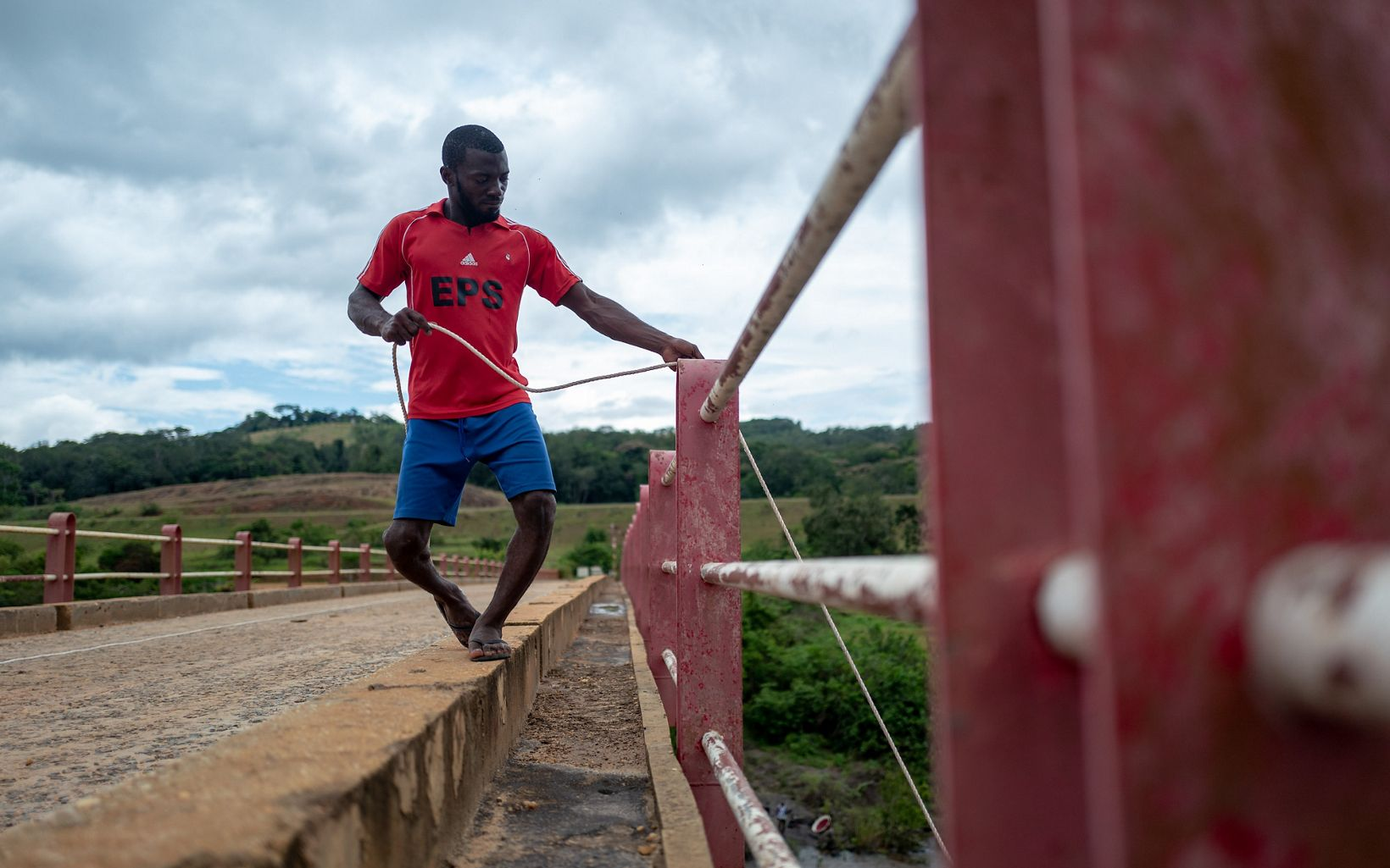 Man holds a rope off a bridge