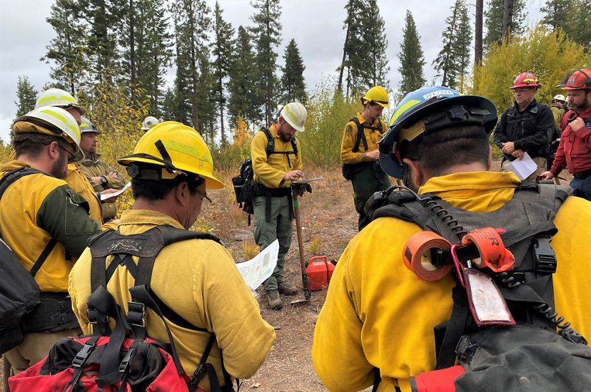 A wildland fire worker explains directions to other fire workers, all dressed in fire-protective garb.