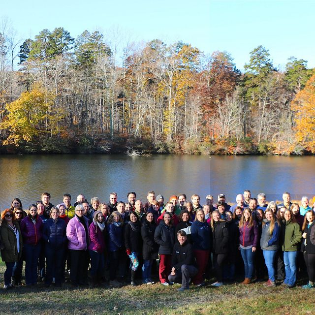 Group photo of TNC VA staff. A large group of people stand together outdoors in front of a calm lake, smiling during the chapter's annual staff retreat.