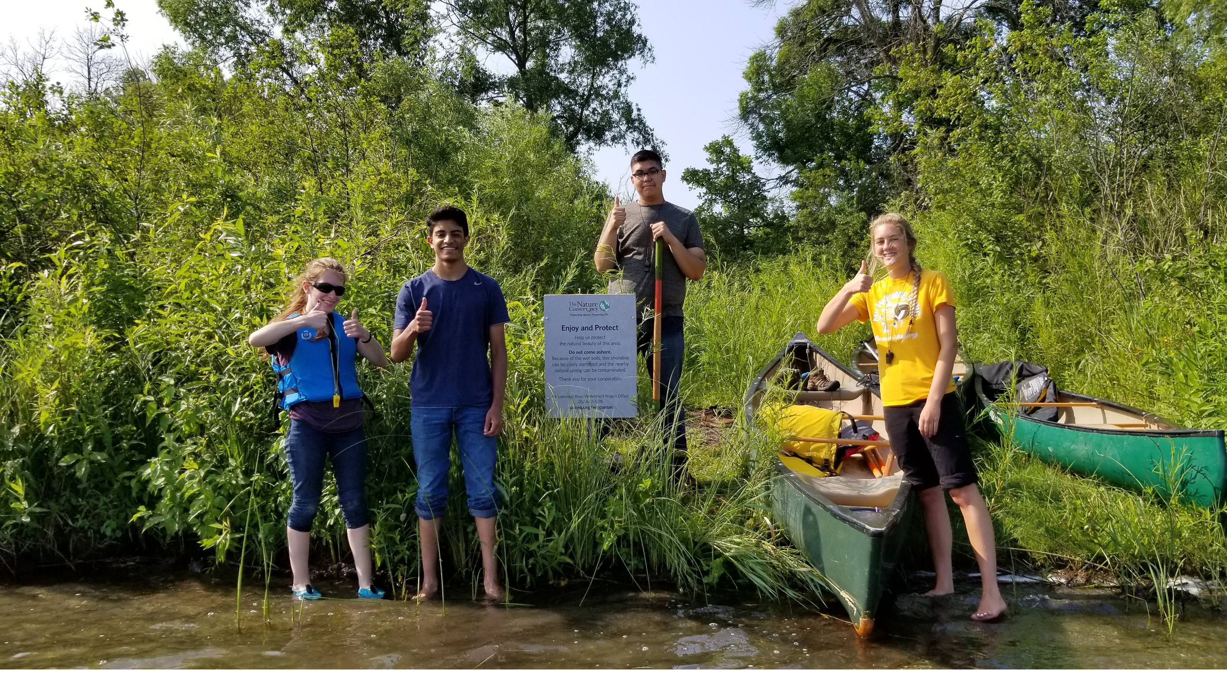 Two young men and two young women stand on the shore and in the shallow water of Lulu Lake next to 2 canoes smiling and giving the thumbs up sign
