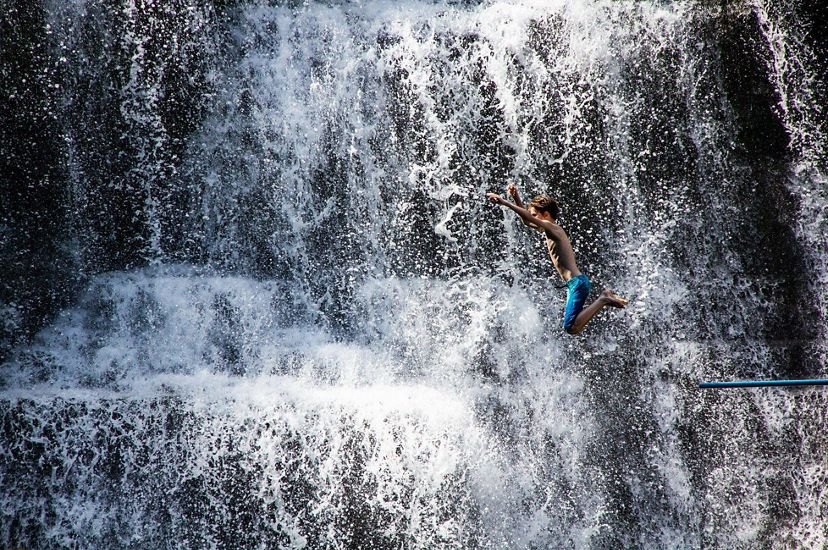 boy jumps into a waterfall
