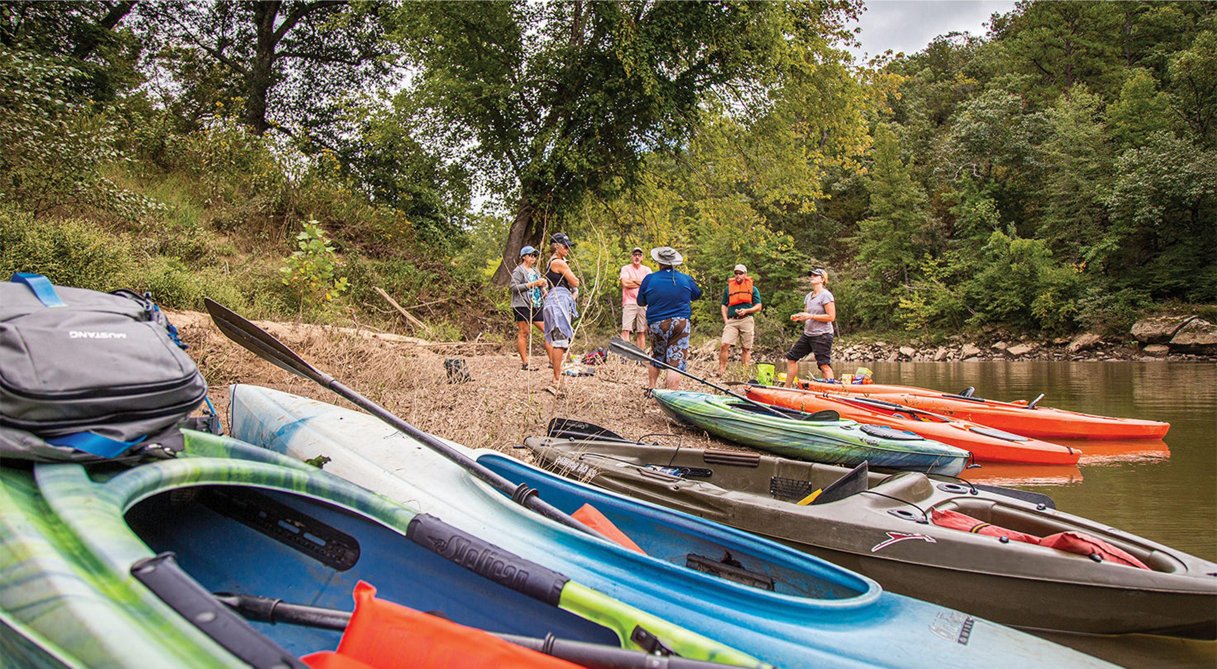 A group of people standing on a sandbar in front of a row of colorful kayaks on the Kiamichi River.