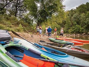 A group of people standing on a sandbar in front of a row of kayaks on the Kiamichi River.