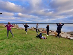 Six children strike silly poses at a park on the edge of the Chesapeake Bay. Puffy white clouds hang low over them in a blue sky.