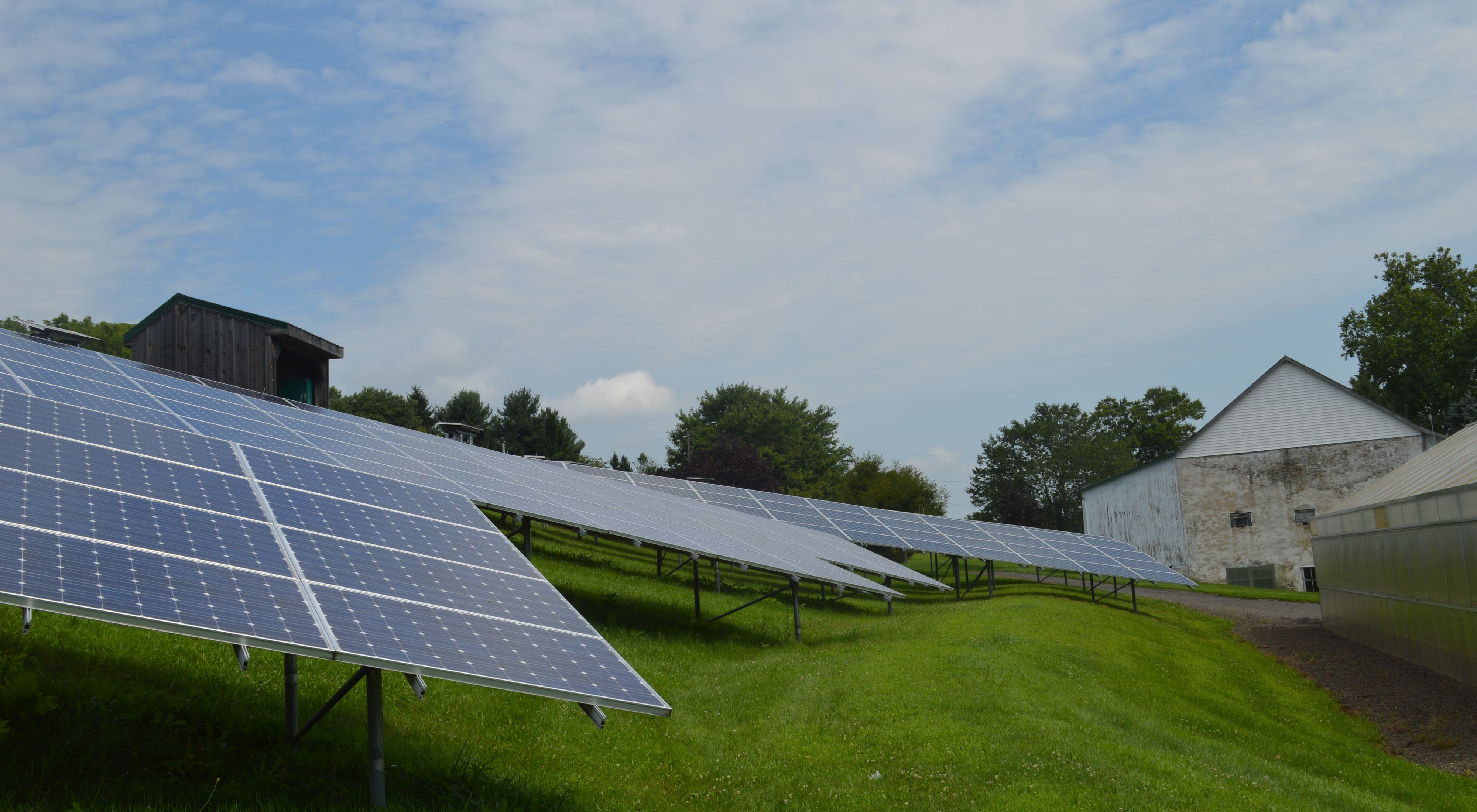 Solar panels on grassy foreground, barn in background.