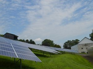 Four large solar panel arrays are nestled into a sloping green patch of land, tucked between two barns on a Pennsylvania farm.