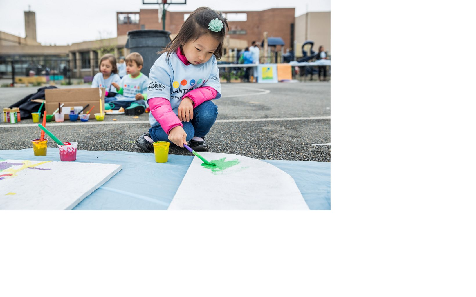 young girl paints sign outdoors
