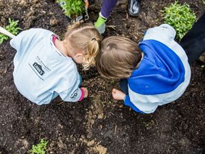 Two young children crouch next to each other over a small hole in a garden. The tops of their heads are just touching as they each prepare to drop a seed into the hole.