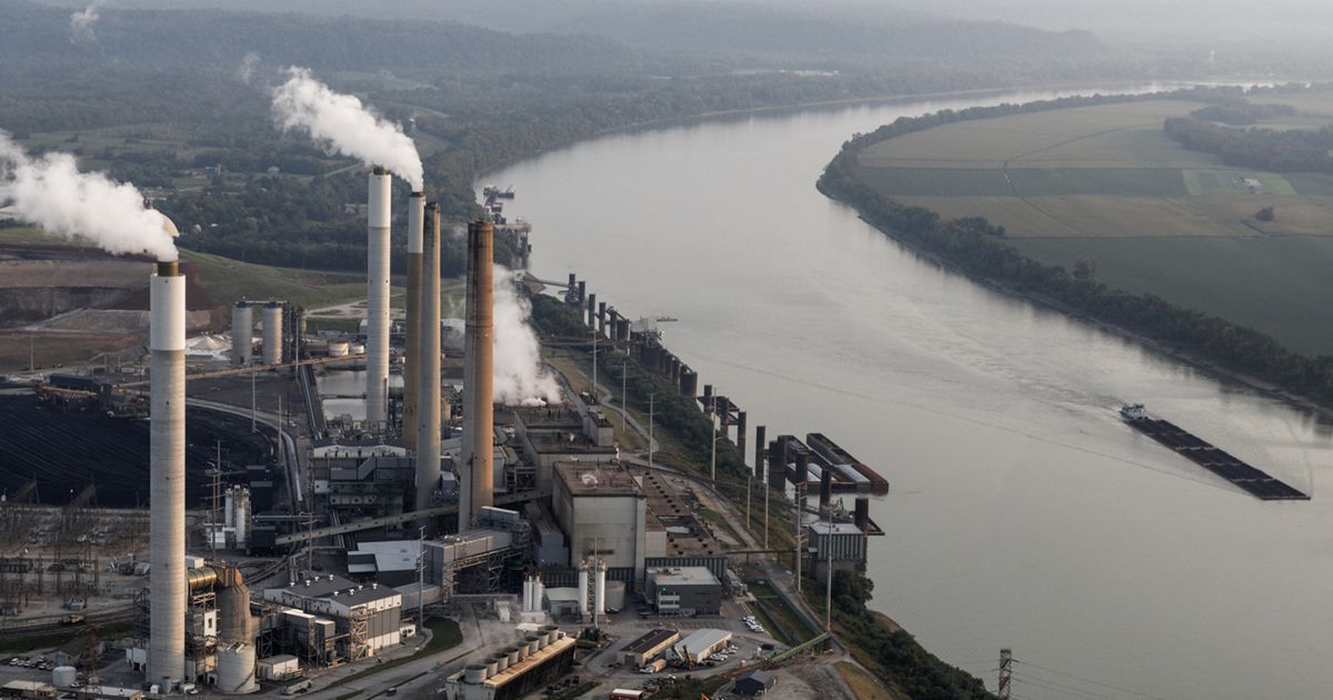 Pollution emerges from a power plant located next to a creek.