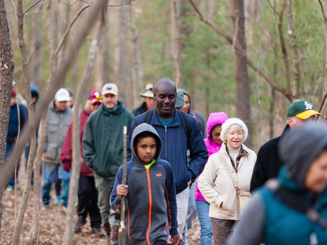 A large group of people walk along a path through a forest. The diverse group is bundled up against the early spring chill.