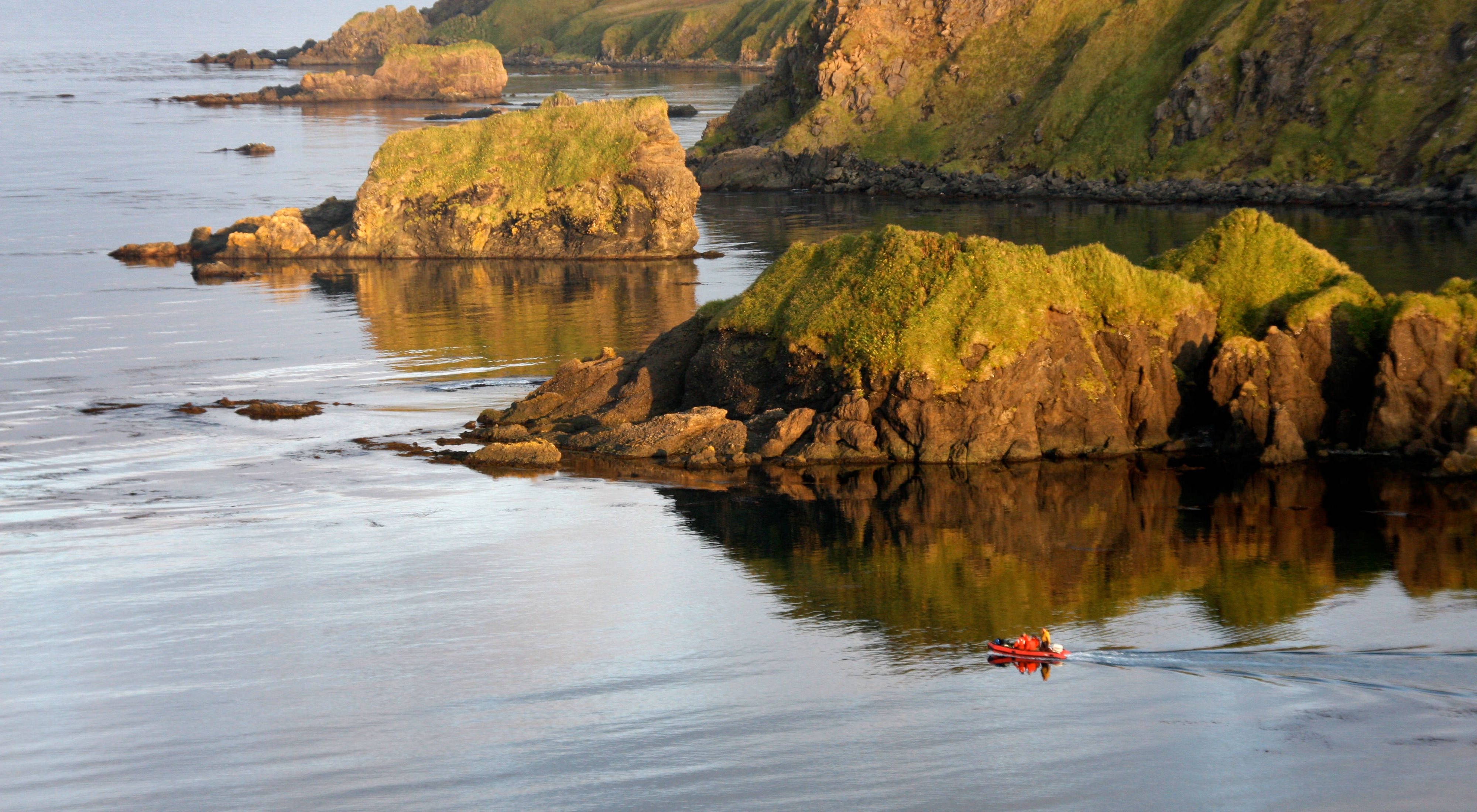 A small red dinghy is dwarfed by the rocky shoreline of Hawadax Island.