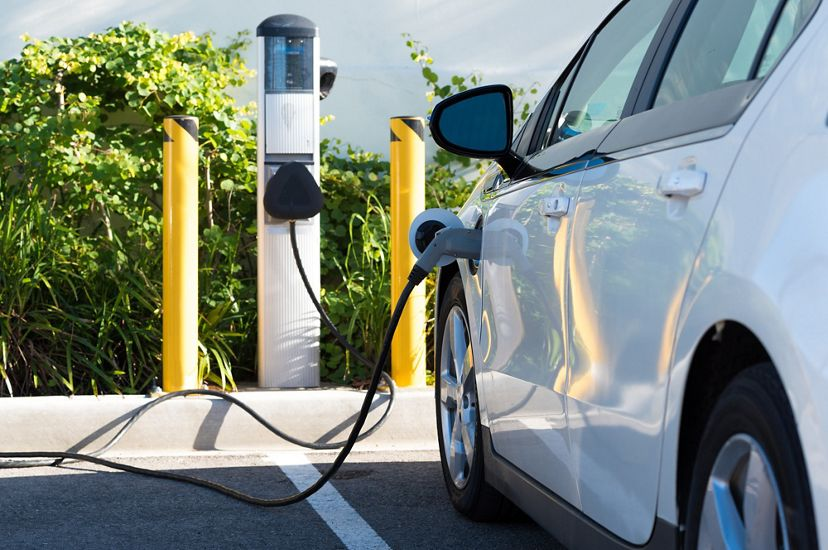 A white car is parked in front of an electric charging station. A heavy black cord is plugged into the car.