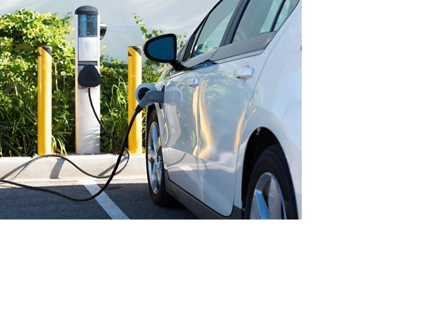 A white car is plugged into a source of electricity.