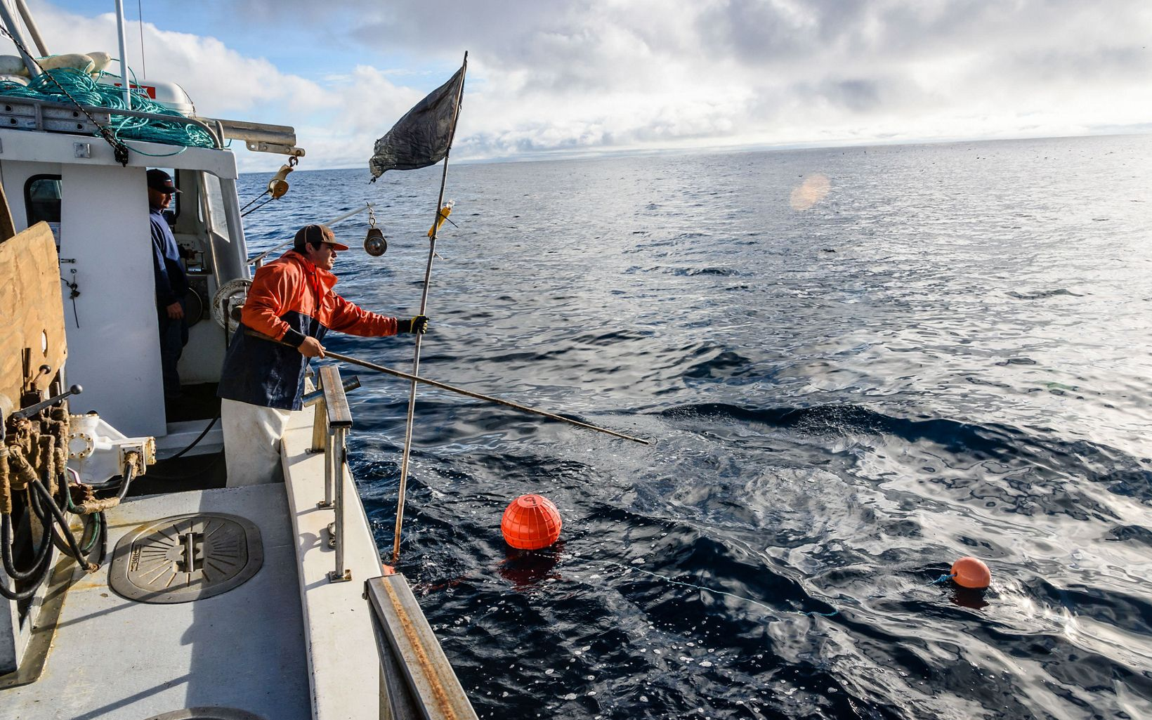Fisherman holding a flag and stick, leaning over the side of a boat with orange buoys floating the water.