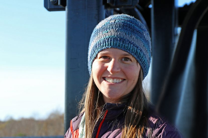 Candid headshot of Stream Restoration Ecologist Holly Lafferty. A smiling woman wearing a blue stocking cap poses and smiles while standing on a bridge.