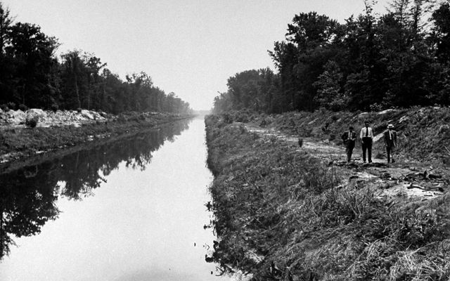 Black and white photo taken in 1943. Three men walk along a narrow river channel. The banks on either side are piled with soil forming high berms.
