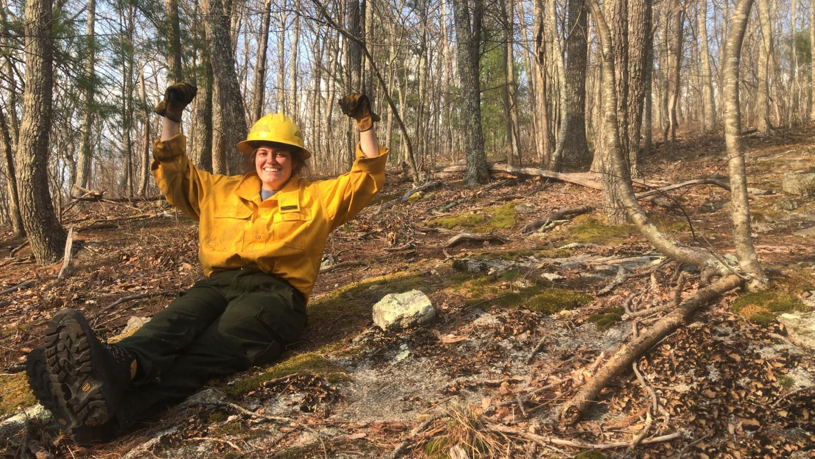 A woman wearing yellow fire gear sits on the ground in a forest. She is smiling and her arms are raised over her head in an expression of celebration.