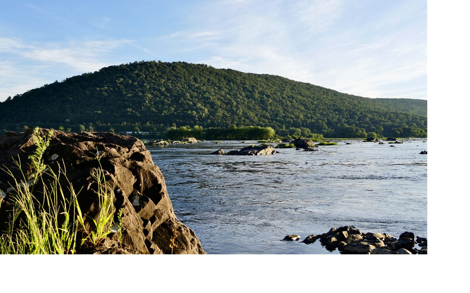 View of Cove Mountain from the east bank of the Susquehanna River. A large boulder is in the foreground. There are ripples on the surface of the water.