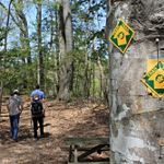 Three people walk past a picnic table following a leaf covered path into a thick green forest. A yellow and green trail blaze sign nailed to a tree marks the way forward.