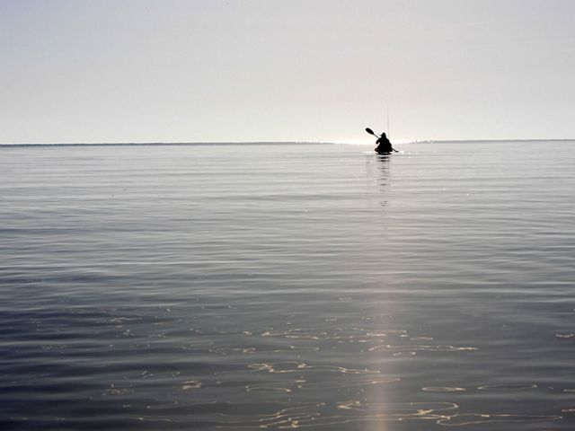 A person floats in a kayak in a flat, wide body of water. They are silhouetted against the sky and seem to hover in the distance at the horizon.