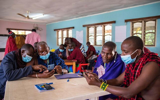 People in a classroom looking at mobile phones