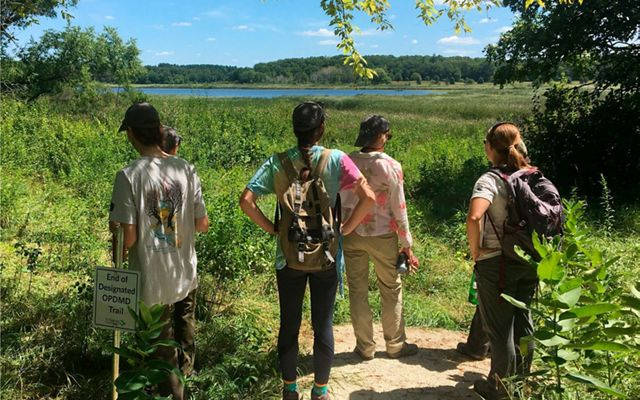 A small group of people stand at end of a trail and look out at wetlands with lake and forested shoreline in the distance