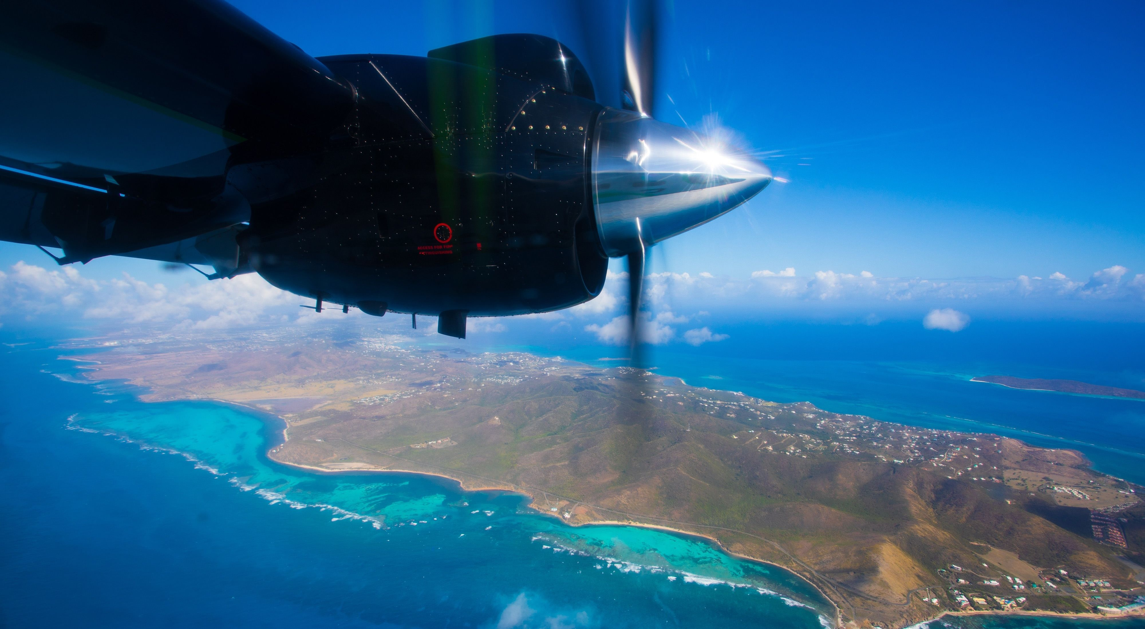 A view of the underbelly of an aerial imaging plane flying over an island with hills and ocean waves in sight.